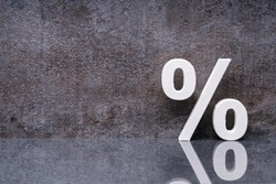 Close-up Of A Percentage Sign Leaning On Dark Wall