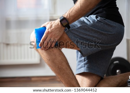Close-up Of A Person Applying Ice Bag On An Injured Knee In The Gym Stock photo ©