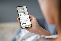 Close-up Of A Person Holding A Smart Phone Using Online Low Prices Hotels Application