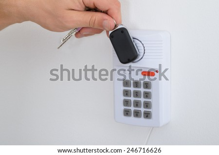 Close-up Of A Person Holding House Keys Arming A Security System