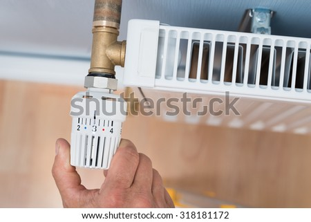 Close-up Of A Person's Hand Adjusting Temperature Of Radiator Thermostat