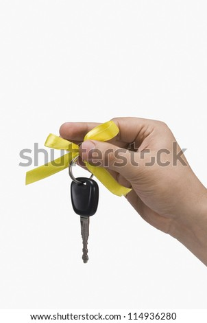 Close-up of a person's hand holding a car key