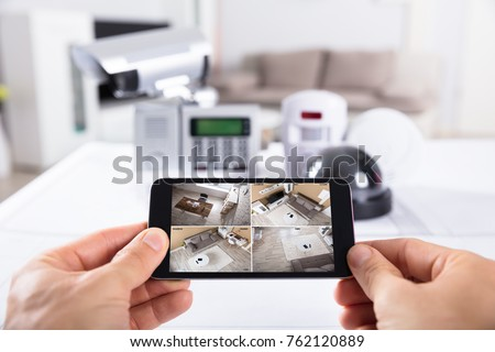 Close-up Of A Person's Hand Holding Mobile Phone With CCTV Camera Footage On Screen