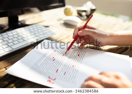 Close-up Of A Person's Hand Marking Error With Red Marker On Document Stock photo ©
