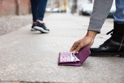 Close-up Of A Person's Hand Picking Up Lost Purse