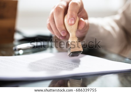 Close-up Of A Person's Hand Stamping On Approved Application Form Over The Desk