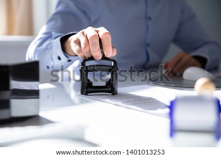 Close-up Of A Person's Hand Stamping With Approved Stamp On Document At Desk