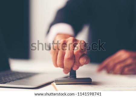 Close-up Of A Person's Hand Stamping With Approved Stamp On Document At Desk, notary or business people work from home, isolated for coronavirus COVID-19 protection Photo stock ©