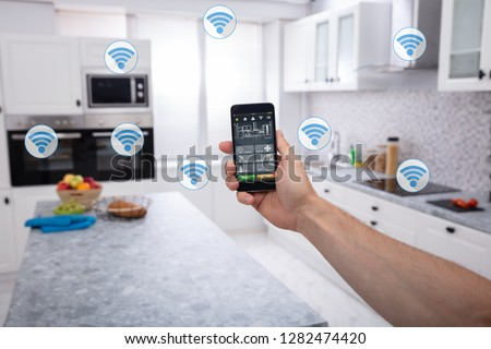 Close-up Of A Person's Hand Using Smart Home System Application On Mobilephone