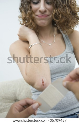 Close-up of a person\'s hands putting a bandage on a teenage girl\'s wounded elbow