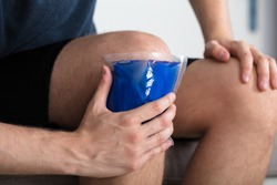 Close-up Of A Person Sitting And Applying Ice Gel Pack On An Injured Knee