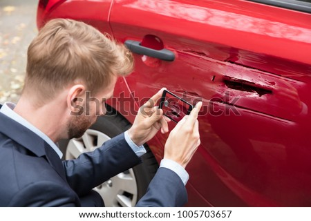 Close-up Of A Person Taking Picture Of Damaged Car On Mobile Phone
