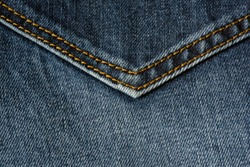 Close-up of a piece of blue jeans with orange stitches. Pocket close-up.