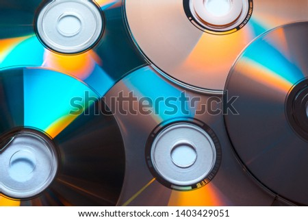 Close-up of a pile of CD or DVD discs with colored reflections