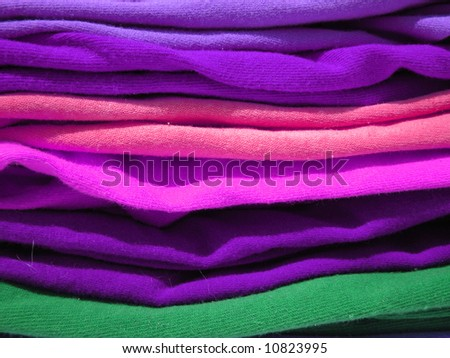 close up of a pile of colorful tshirts freshly folded from the laundry