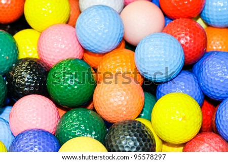 Close up of a pile of multi-colored golf balls