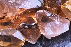 Close-up of a pile of raw translucent Rauchtopaz (Smoky quartz) mineral stone. Macro shooting of specimen of natural mineral. Several smoky quartz raw stones as a background. Selective focus.