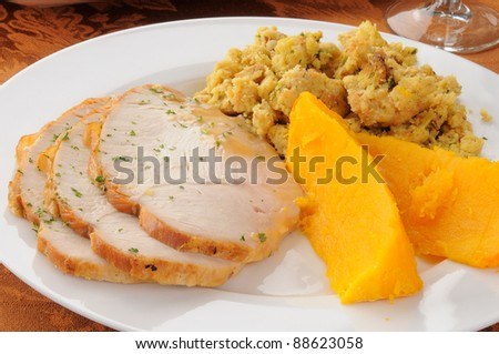 Close up of a plate of sliced turkey breast, butternut squash and dressing