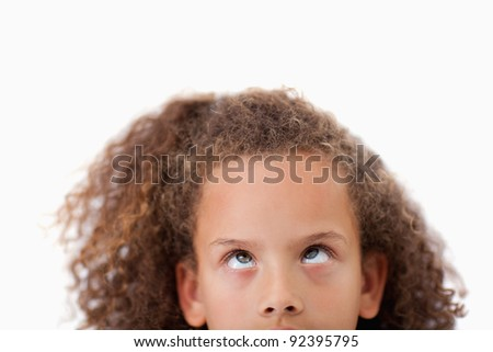 Close up of a playful girl looking above her against a white background #92395795