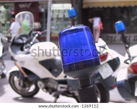 close up of a police light with a police motorcycle in the background