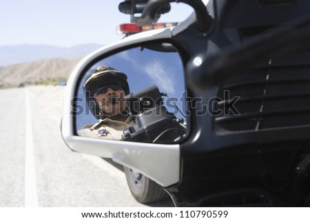 Close-up of a police officer reflecting in side view mirror