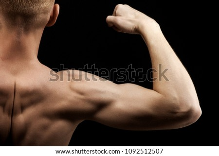 Close-up of a power fitness man's hand. Strong and handsome young bodybuilder demonstrate his muscles and biceps.