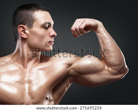 Close-up of a power fitness man\'s hand. Strong and handsome young bodybuilder demonstrate his muscles and biceps