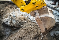 Close up of a power shovel/excavator digging road.