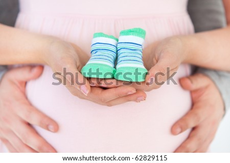Close-up of a pregnant woman holding baby shoes and of her husband at home
