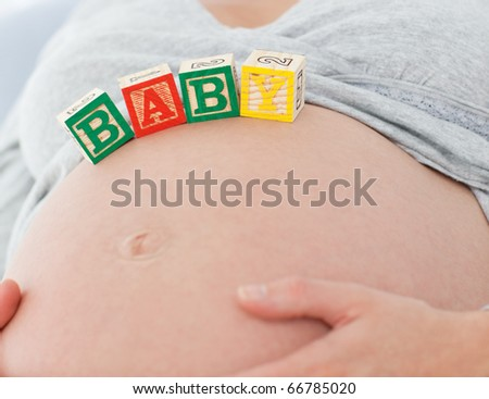 Close up of a pregnant woman with baby letters on her belly on the bed