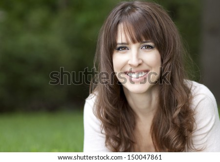 Close-up of a pretty woman on the grass smiling