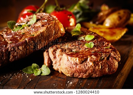 Close up of a rare roasted juicy medallion of beef fillet seasoned with salt and spices and garnished with fresh herbs served on a wooden board
