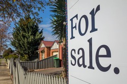 Close up of a real estate sign board with text  'for sale' , some suburban houses/Australian homes and pedestrian walkway as background. Concept of selling property and real estate market/investment.