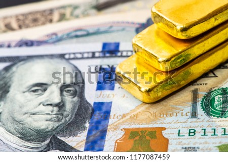 Close-up of a real gold bullion and international currencies america US dolla banknote is a safe haven of investment and wealth concept.