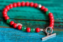 Close up of a red and green beaded bracelet with a silver clasp. The jewelry lies on a wooden colored table in a vintage style.