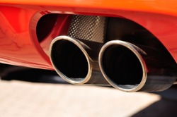 Close up of a red car dual exhaust pipe