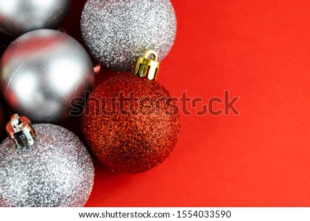 Close up of a Red glitter covered Christmas Tree bauble surrounded by other baubles which are matt silver and red glittered baubles set against a red background. #1554033590
