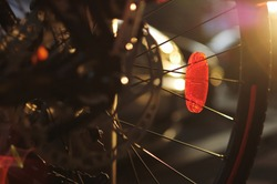 Close up of a red reflector on the bicycle wheel, detail of spokes, brake and wheel rim in backlight. Safety device. Bike wheel reflector.