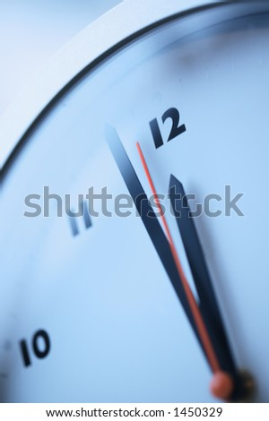 Close up of a red second hand approaching midnight on a wall clock