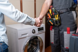 Close-up of a repairman shaking hands with a female customer. Male repairman for washing machine repair