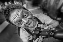Close-up of a reporter / photographer with camera and crazy comical face