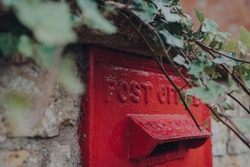 Close up of a retro red mailbox in Cotswolds, UK, selective focus, framed by an ivy plant.