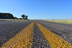 Close-up of a road with double yellow lines going off into the horizon under a clear blue sky in Badlands National Park, South Dakota.