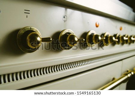 Close up of a rob of  golden chrome knobs of an old style kitchen