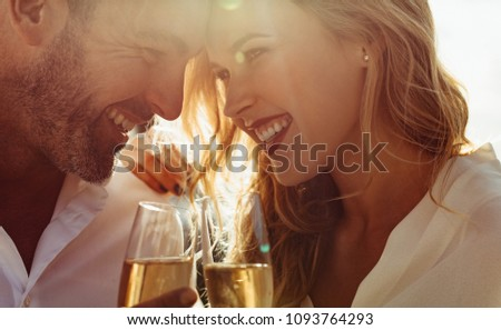 Close up of a romantic couple with their heads together holding a glass of wine. Couple with wine smiling outdoors.