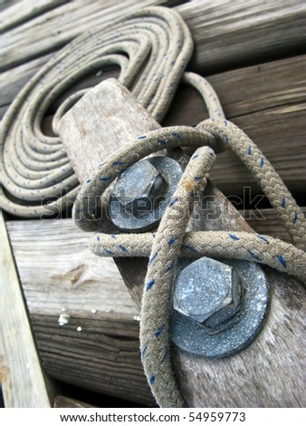 Close up of a rope tied onto cleat dockside
