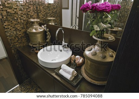 close-up of a round countertop washbasin, next to the brass vase with purple roses and three towels, the wall is coating with mosaic tiles