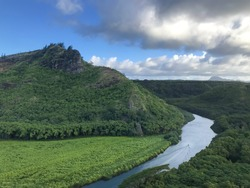 Close up of A round high round mountain covered with trees on the horizon. Panorama Aerial scene view of a mountain river with a boat sailing. kamokila hawaiian village, Kauai, Hawaii islands, U.S.A
