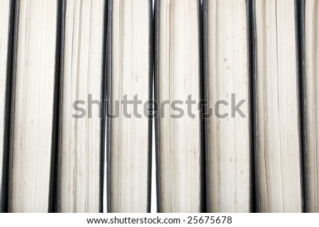 Close-up of a row of old marked antique books, leather-bound with white background light through the gaps between books