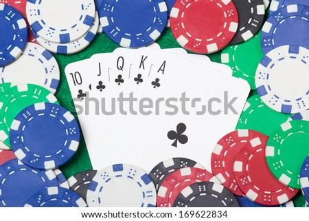 close up of a royal flush combination at poker with chips on the green casino table